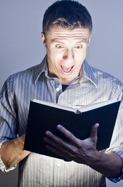 man gasping in surprise over a book.