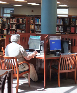 man using a computer at the Courtice Branch.